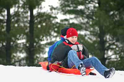 kids sledding in the snow